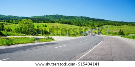 Wide road and rural landscape with green hills