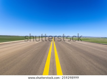 wide road in prairie against a blue sky - stock photo