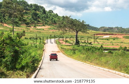 Wide road to green hill - stock photo