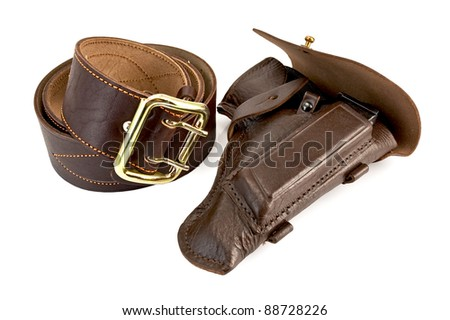 Wide roll of brown belt with a shiny yellow buckle and holster the gun out of the skin is isolated on a white background - stock photo