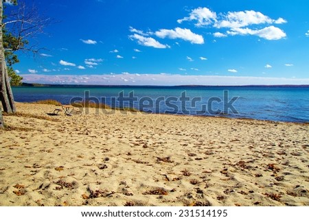 Wide sandy beach and an aquamarine horizon. North Higgins Lake State Park encompasses much of the shore of Higgins Lake; voted the sixth most beautiful lake in the world by National Geographic.  - stock photo