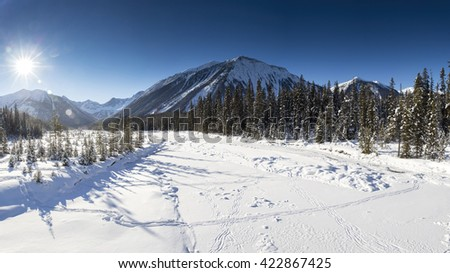 Wide scenic winter panorama of a frozen snow covered river in Canada, clear blue sky, mountains in the background, flanked by pine trees, sun setting to the left of the frame - stock photo