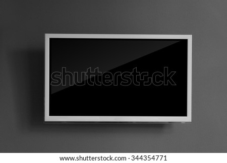 Wide screen television on grey wall background - stock photo