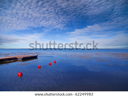 Wide  sea with red buoys - stock photo