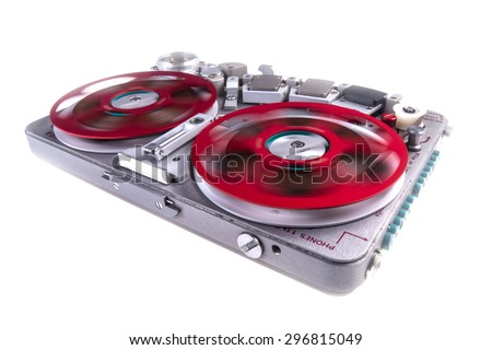 Wide shot of a reel to reel audio tape recorder with spinning reels on white background