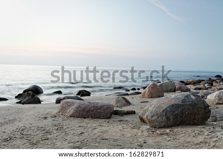 wide shot of a sunset at the horizon, reflecting on a smooth sandy beach with huge stones at beautiful polish Baltic Sea, vacation travel concept - stock photo