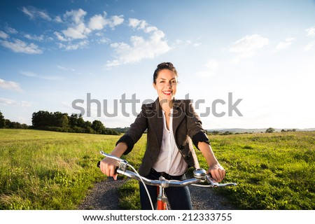 Wide shot of beautiful young woman on retro orange bicycle at sunset in countryside. Active summer. Vintage feeling. Low depth of field. Strong sun and dark long shadows.
