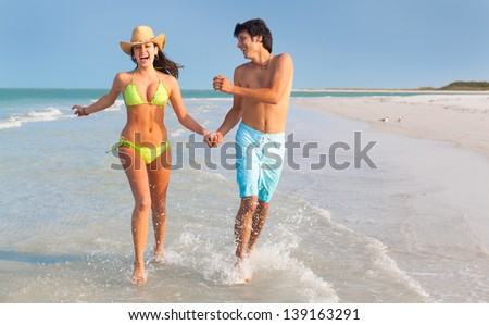 wide shot of Latin young Man and Woman running through surf and holding hands on Florida Beach - stock photo