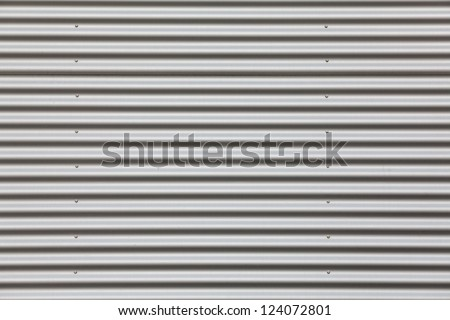 Wide shot of silver corrugated metal with bolts - stock photo