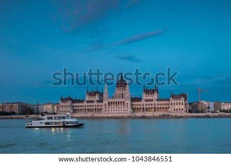 Wide shot of the Hungarian Parliament on the River Danube Budapest. Taken  at dusk from the opposite bank of the river as a small tour boat passes