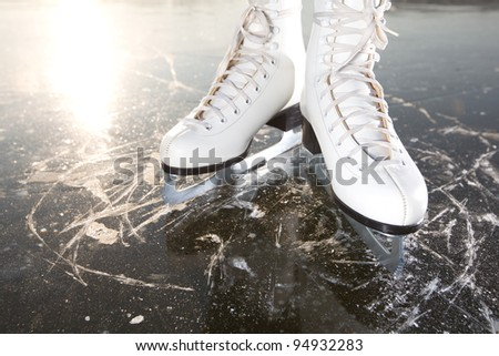 Wide skates on ice with sun reflected in behind - stock photo