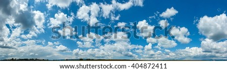 Wide sky panorama with scattered cumulus clouds - stock photo