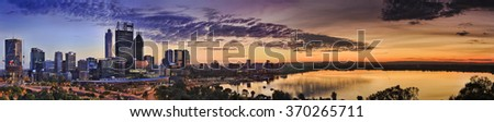 wide sunrise panorama of Perth CBD cityscape with swan river reflecting warm yellow sun light from elevated lookout in Kings park - stock photo