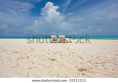 wide tropical beach with beach chairs - stock photo
