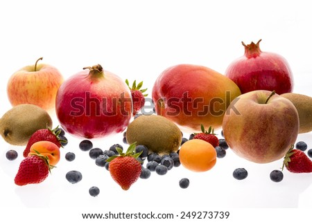 Wide variety of assorted whole fruit isolated on white. Ripe strawberries, blueberries, apricots, kiwi fruits, apples, pomegranates and mango. Fresh multivitamin arrangement. Closeup. Selective focus. - stock photo