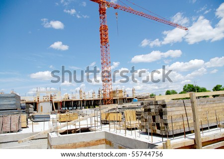 wide view landscape of construction work in progress with building material foundation in the foreground and industrial crane in the background horizon sky. blue red yellow dominant colors - stock photo