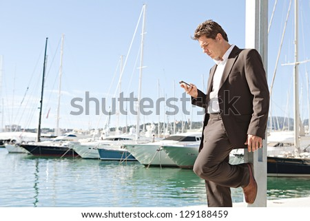 """Wide view of a businessman using his """"smart phone"""" while standing near a marine with luxury yachts against a deep blue sky and sea. - stock photo"""