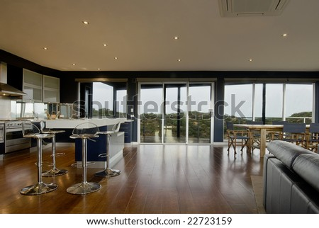 Wide view of a deluxe living area. Kitchen, dining with scenic view from the windows. - stock photo