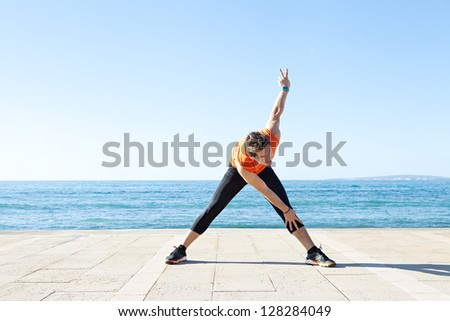 Wide view of a sports man body figure stretching on a track along the sea with the blue sky in the background and open space around him. - stock photo
