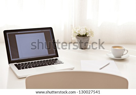 Wide view of a work desk interior with a laptop computer and white curtains on a sunny day. - stock photo