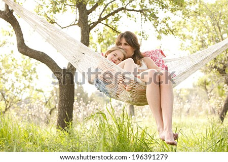 Wide view of a young mother and daughter relaxing together and smiling sitting in a hammock, hugging and lounging during a sunny summer day in a holiday home garden with grass and trees, lifestyle. - stock photo