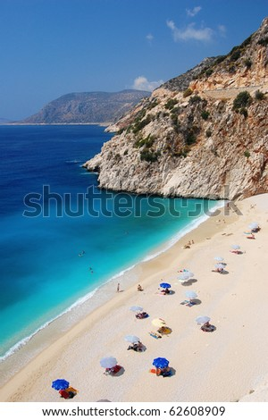 Wide view of amazing blue water on a small beach on the coast of Turkey, with umbrellas scattered across the beach. - stock photo