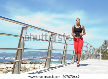 Wide view of an athletic young african american woman running and exercising by the seaside during a sunny day. Health and fitness body care and training outdoors. - stock photo