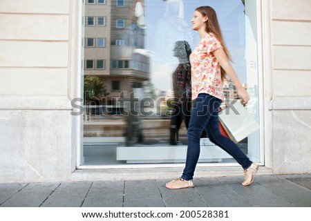 Wide view of an attractive young woman walking passed a shopping mall with a large store window reflecting city buildings, carrying shopping bags. Dynamic and fun consumer lifestyle, outdoors. - stock photo
