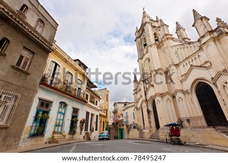 Wide view of an urban scene in Old Havana with a view of typical houses and  the Santo Angel Custodio Church
