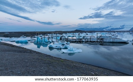 Wide view of blue icebergs floating in Jokulsarlon glacial lagoon at dusk, Iceland