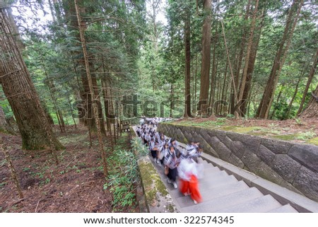 Wide view of blurred pupils visiting Japanese temple, climbing stairs - stock photo