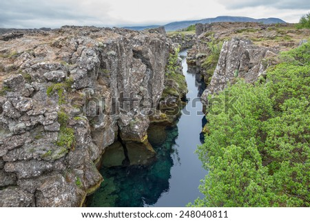 Wide view of National Park of Thingvellir with stream and rocks in Iceland - stock photo