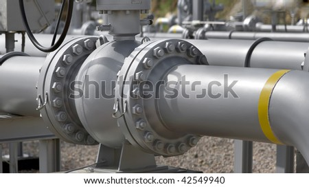 Wide view of pipe flanges from an LPG station. Panoramic picture, not a crop. - stock photo