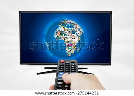 Widescreen high definition TV screen with sphere video gallery. Remote control in hand - stock photo