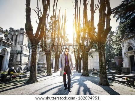 widower walk into a cemetery - stock photo