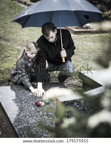Widower with little girl daughter at graveyard - stock photo