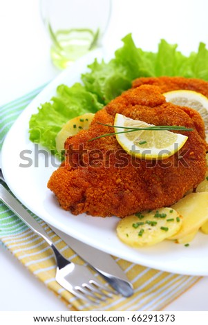 Wiener Schnitzel, breaded with potato salad - stock photo