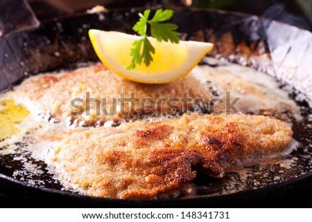 wiener schnitzel frying in a pan  - stock photo