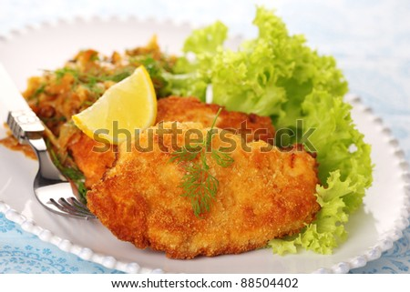 Wiener Schnitzel on white plate with salad and lemon.