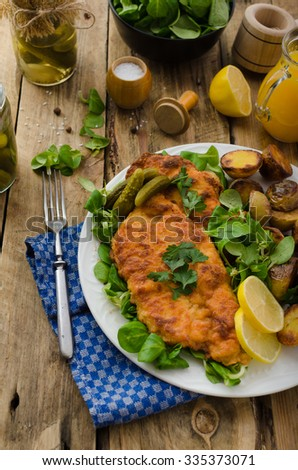 Wiener Schnitzel, served with baked potatoes, pickled cucumbers and freshly squeezed orange juice - stock photo