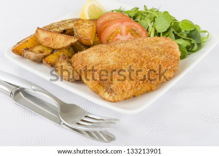 Wiener Schnitzel - Veal steak breaded and fried in butter served with salad, potato wedges and a lemon slice. - stock photo