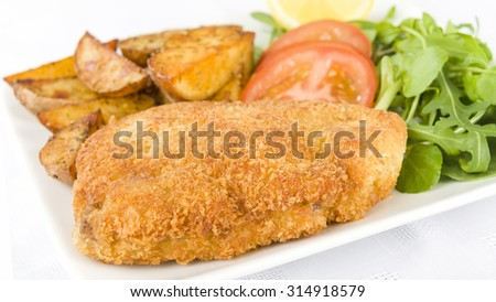 Wiener Schnitzel - Veal steak breaded and fried in butter served with salad, potato wedges and a lemon slice.