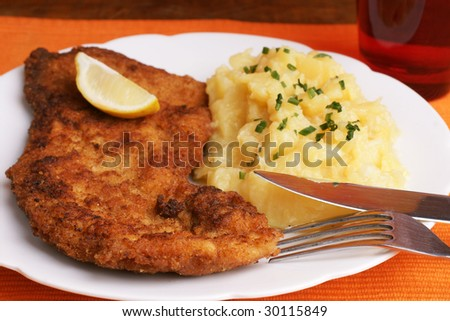 Wiener Schnitzel with potato salad topped with chopped chives. - stock photo