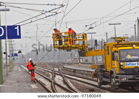 WIESBADEN, GERMANY - FEBRUARY 2: workers repair the catenary on February 2,2011 in Wiesbaden, Germany. The equipment is rented by Boehls, the leading rental company in Europe. - stock photo