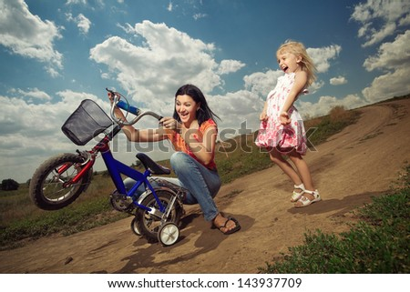 Wiew of happy mother teaching little girl how to ride a bicycle
