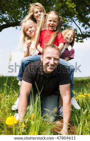 Wife and daughters horse riding daddy - all of them looking happy, the father only a bit