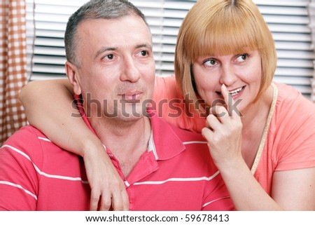 Wife and husband in middle age smiling and looking with interest. Focus on woman. - stock photo