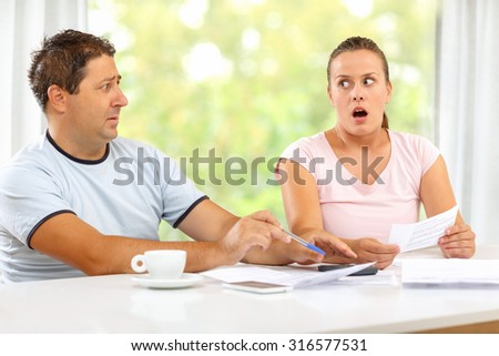 Wife angry at husband for making large bills - stock photo