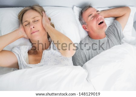 Wife blocking her ears from noise of husband snoring in bedroom at home - stock photo