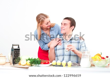 wife embraces the husband, he holds a glass of milk - stock photo